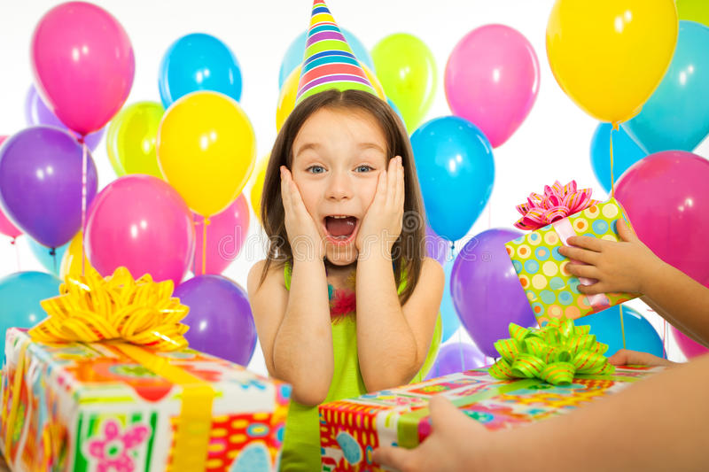 Joyful little kid girl receiving gifts at birthday stock images
