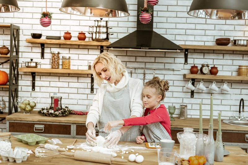 Joyful little kid in red dress sifting flour on dough piece. Mashing piece. Joyful little kid in red dress sifting flour on dough piece while mother working with royalty free stock images