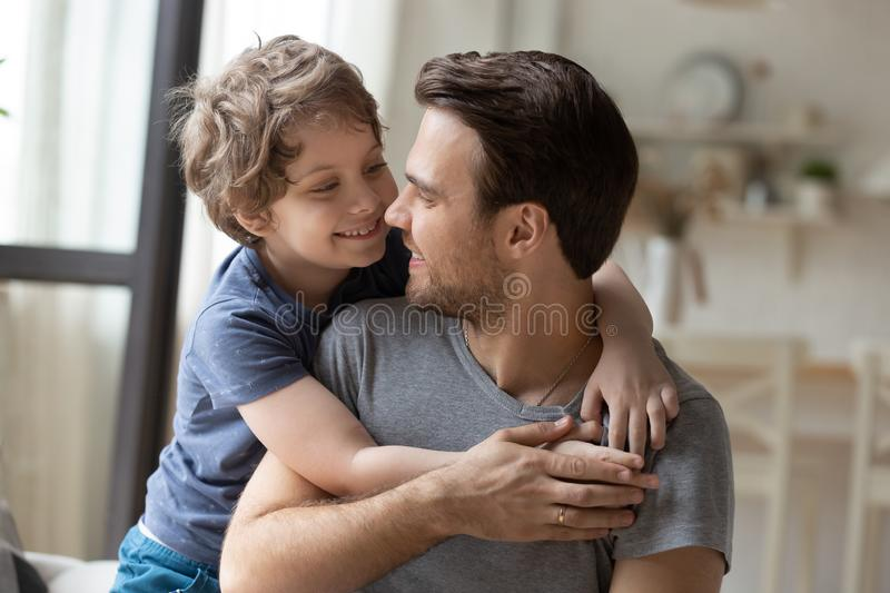 Joyful little preschool boy hugging from back father. Joyful little preschool boy hugging from back smiling young father, head shot close up portrait. Happy stock photos