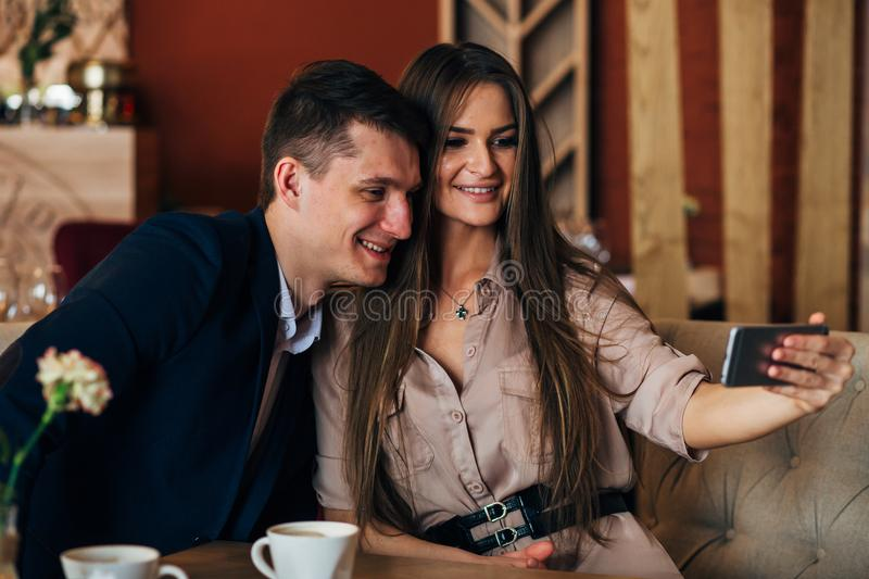 Joyful loving couple enjoying modern technology, having fun, capturing bright moments of vacations in cafe royalty free stock photo