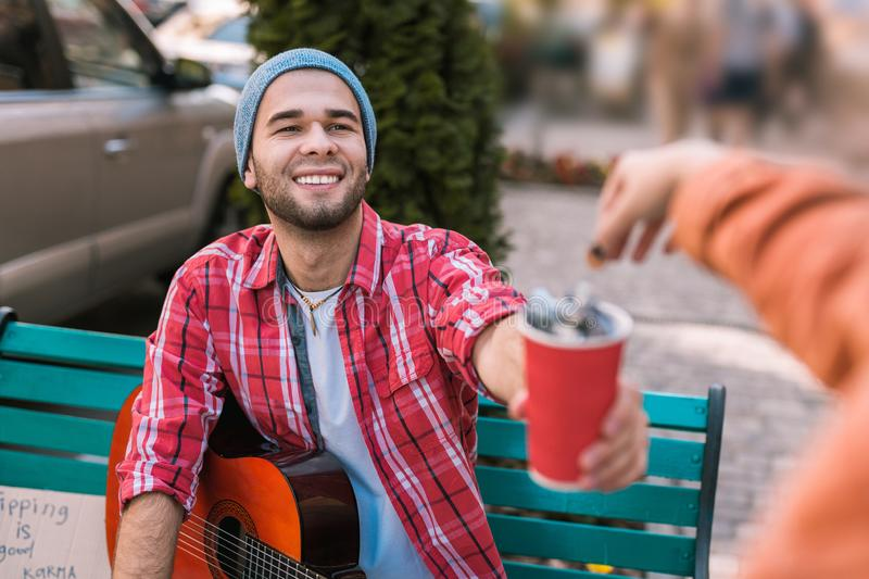 Joyful male guitarist gathering money for play royalty free stock photo