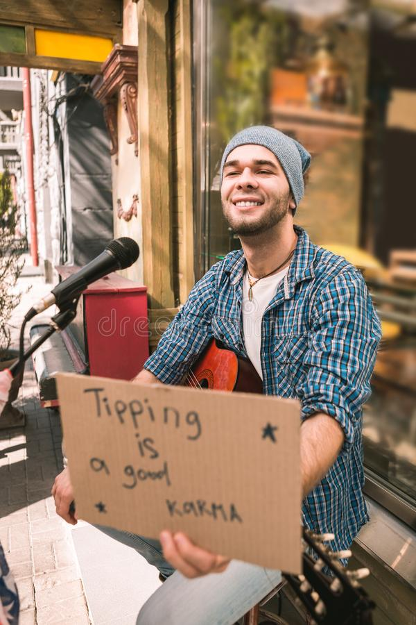 Joyful male musician seeking for tips after play royalty free stock photography