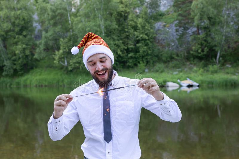 Joyful man in a business suit and santa hat holds sparkler. New Year corporate party. Joyful man in a business suit, tie and New Year or santa hat holds a stock photography