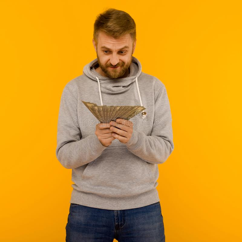 Joyful man in a gray hoodie looks at money dollars on a yellow background royalty free stock images