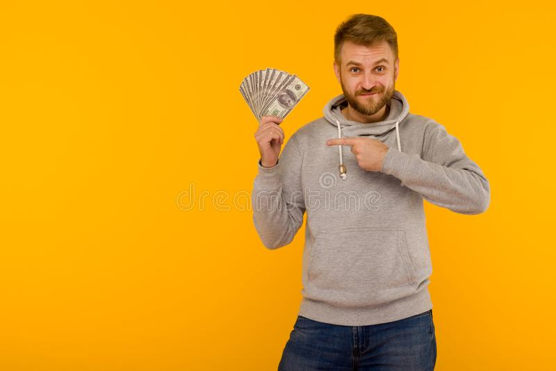 Joyful man in a gray hoodie points a finger at money dollars on a yellow background stock photo