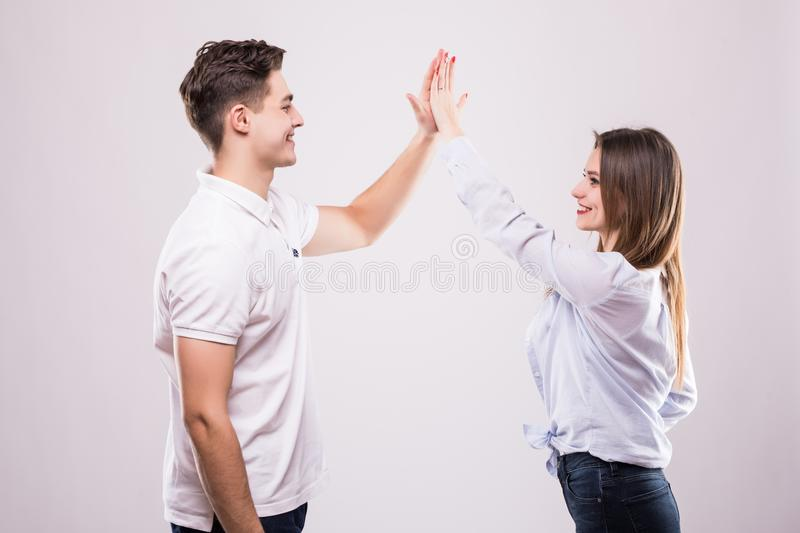 Joyful man and woman greeting each other with a high five on white royalty free stock images