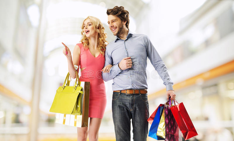 Joyful marriage couple in the shopping mall stock images