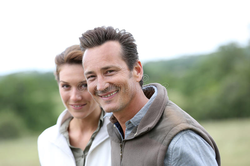 Joyful mature couple walking in countryside royalty free stock images