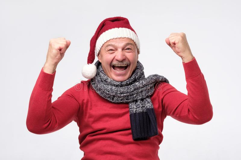 Joyful mature hispanic man in christmas hat is happy with gifts and shouting wow stock photos