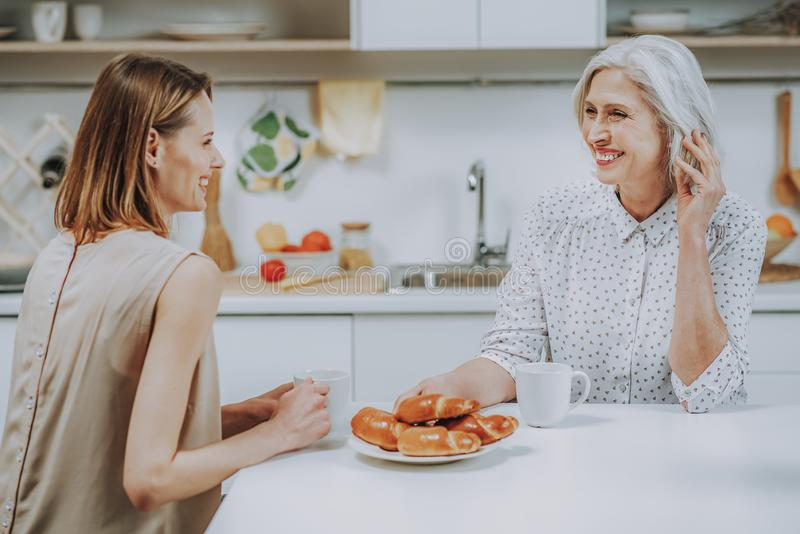 Happy young woman is having breakfast with mother at home stock photos