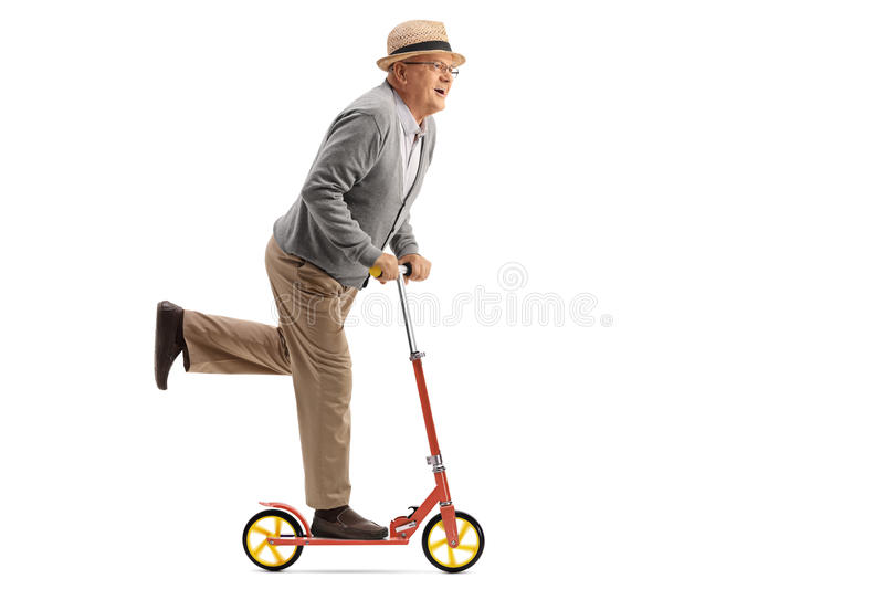 Joyful mature man riding a scooter stock photography