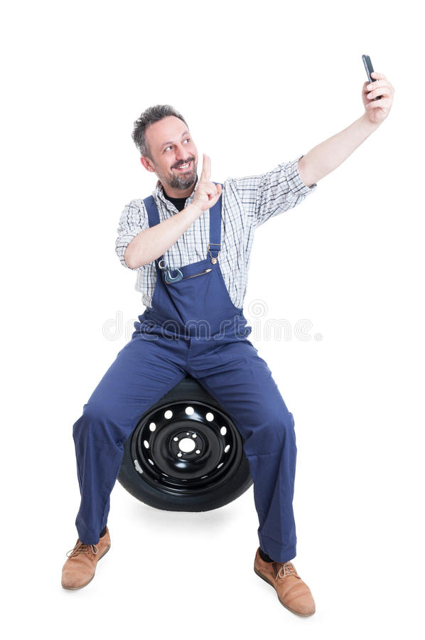 Joyful mechanic sitting on tire and taking selfie royalty free stock images