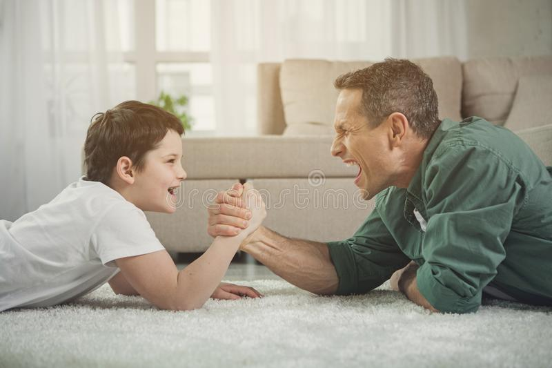 Cheerful father and son playing arm-wrestling at home. Joyful men and boy are competing in arm wrestling while lying on carpet in living room. Child is looking royalty free stock photography