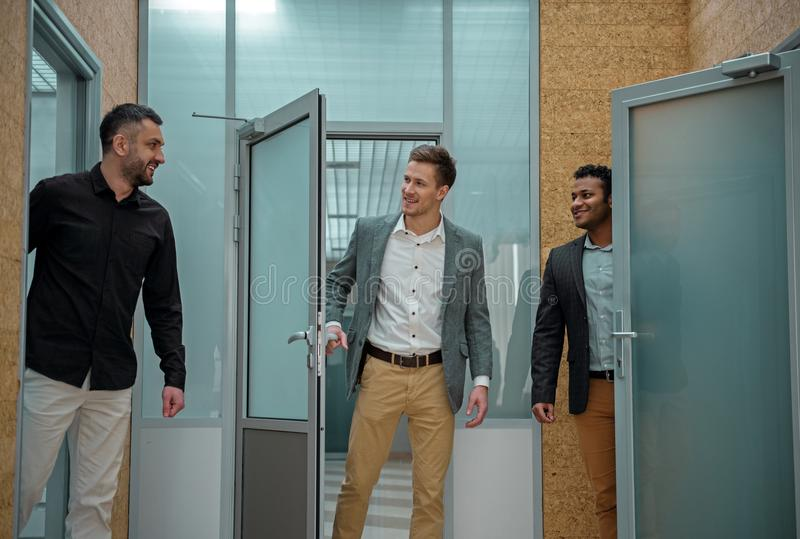 Joyful men are communicating in doorways royalty free stock photography