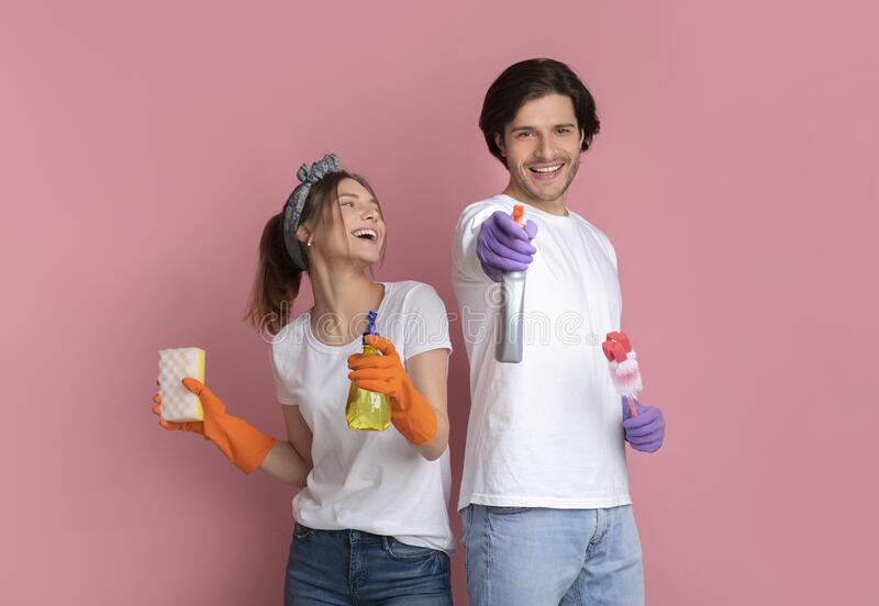 Joyful millennial couple posing with cleaning supplies on pink background. On Guard Of Cleanliness. Joyful millennial couple posing with cleaning supplies on stock photos