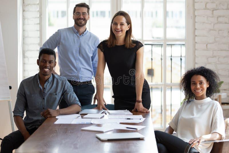 Joyful millennium diverse beroeps verzamelden zich dichtbij lijst stock foto