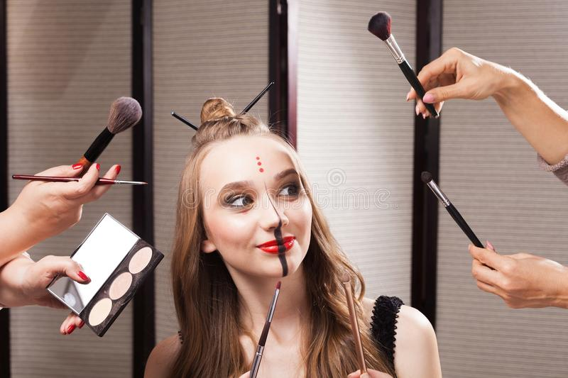 Joyful model surrounded by hands holding brushes. Beautiful young joyful model with professional unusual makeup and a coiffure with topknot and braid made by royalty free stock images
