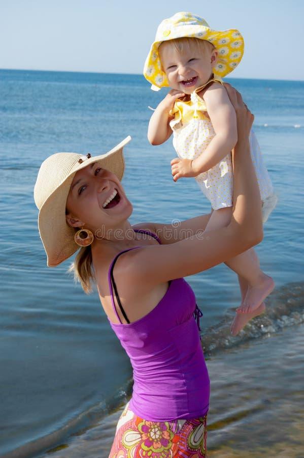 Joyful mother and daughter at beach royalty free stock photos