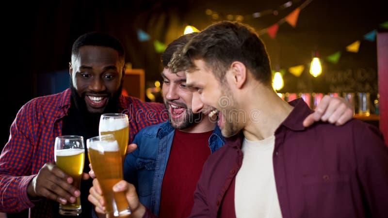 Joyful multiethnic bachelors clinking beer glasses, watching football in pub stock photo