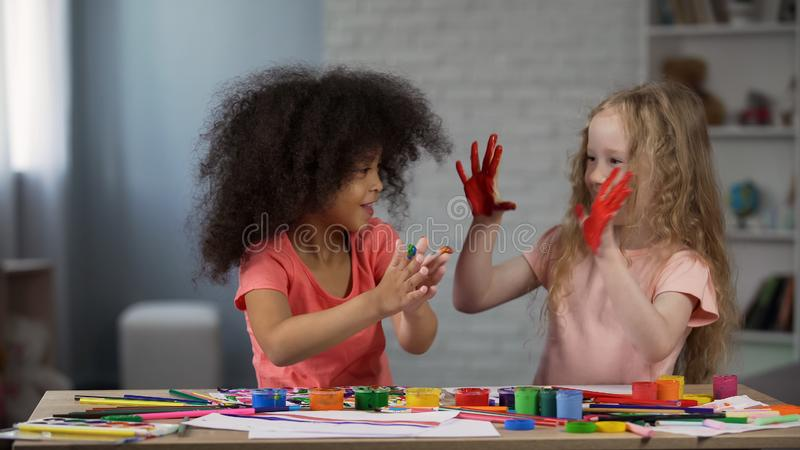 Joyful multiracial kids smudging hands with paints children art club happiness. Stock photo royalty free stock images