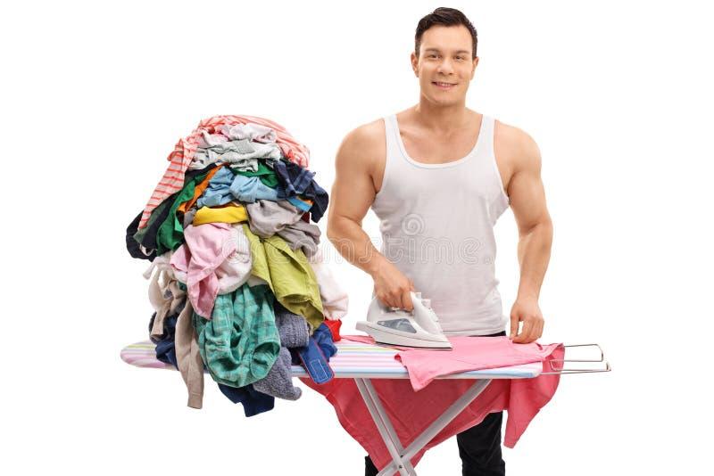 Joyful muscular guy ironing a pile of clothes. Isolated on white background stock photos