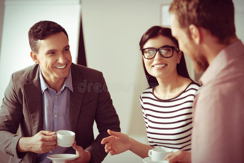Joyful nice colleagues having coffee. Coffee time. Joyful nice delighted colleagues talking to each other and drinking coffee while having a break from work royalty free stock images