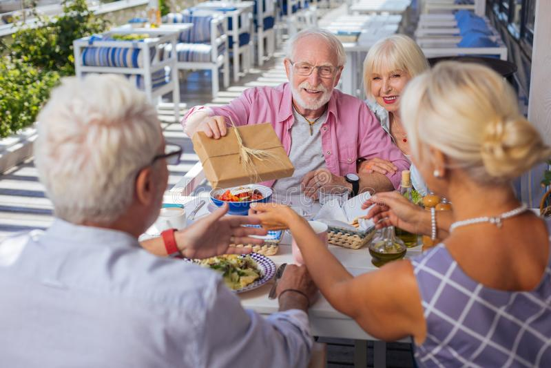 Joyful nice elderly couple congratulating their friends stock images