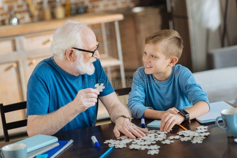 Joyful nice man collecting jigsaw puzzles. Entertaining activity. Joyful nice pleasant elderly men sitting at the table and collecting jigsaw puzzles while royalty free stock photography