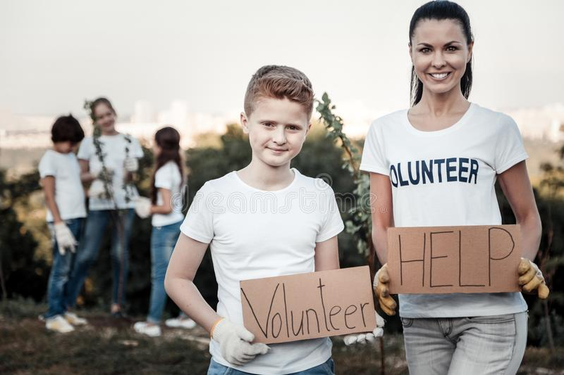 Joyful nice woman holding a volunteer sign stock photography