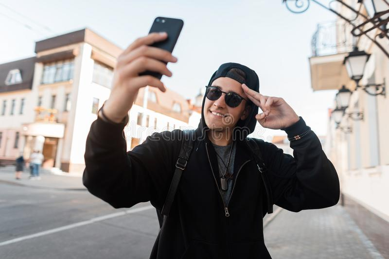 Joyful nice young hipster man in trendy hoodie hooded in dark sunglasses in a stylish cap with a smile makes the selfie outdoors royalty free stock photo