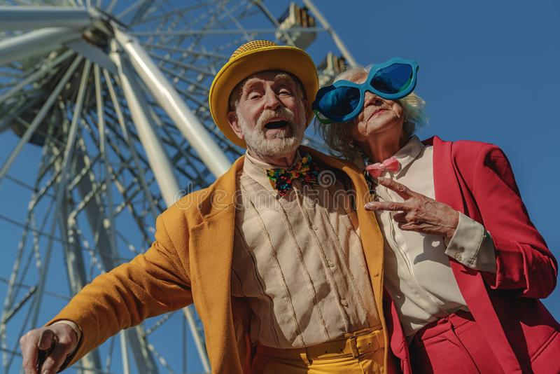 Joyful old couple in ridiculous clothes near attraction stock images