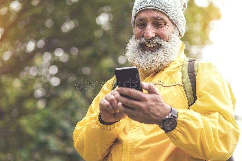 Joyful old man using mobile phone in woodland royalty free stock photography