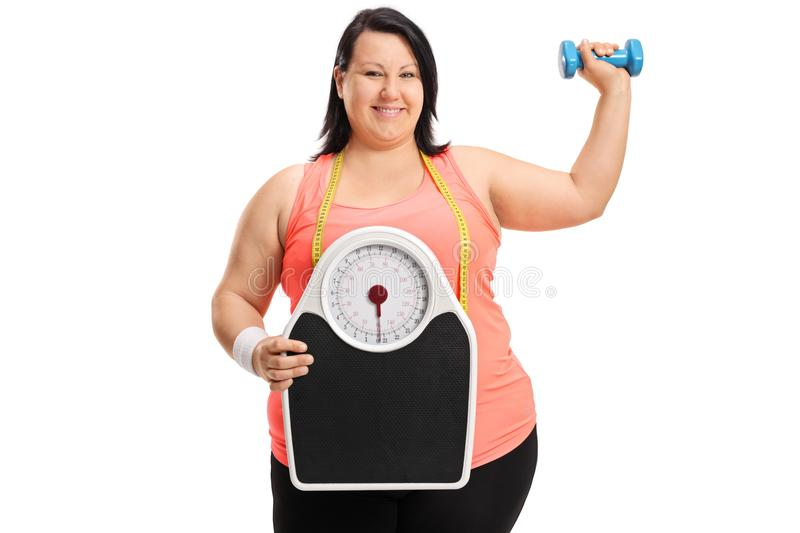 Joyful overweight woman with a weight scale and a small dumbbell. Isolated on white background royalty free stock photos