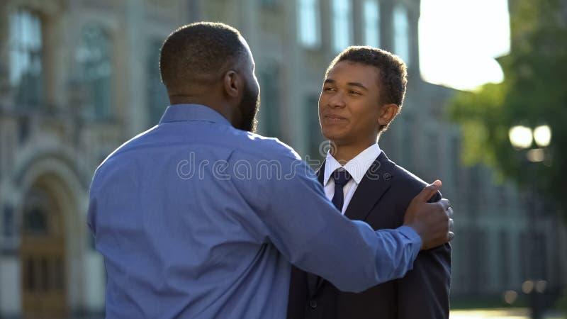 Joyful parent hugging graduating son in suit outdoors academy, prom celebration stock images