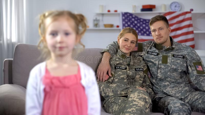 Joyful parents in US military uniform admiring little daughter looking at camera. Stock photo stock photo