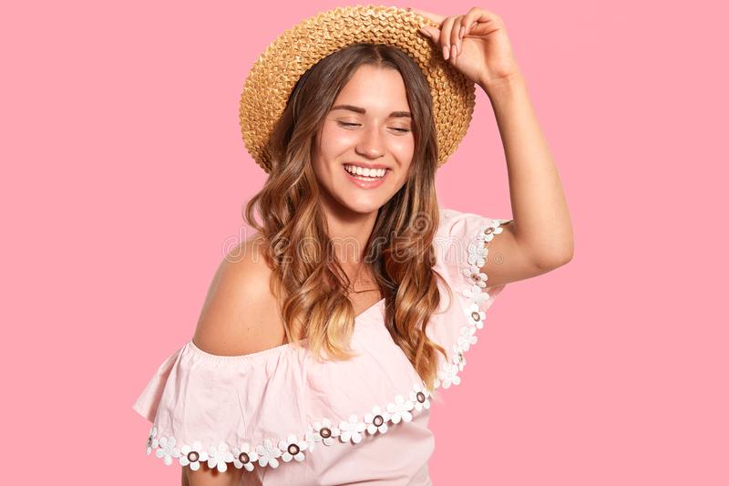 Joyful pleased woman with toothy smile, wears headgear, fashionable blouse, giggles positively, enjoys pleasant moments in life, royalty free stock images