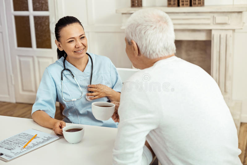 Joyful positive caregiver having tea with her patient. Friendly relationships. Joyful positive female caregiver sitting at the table and having a pleasant stock images