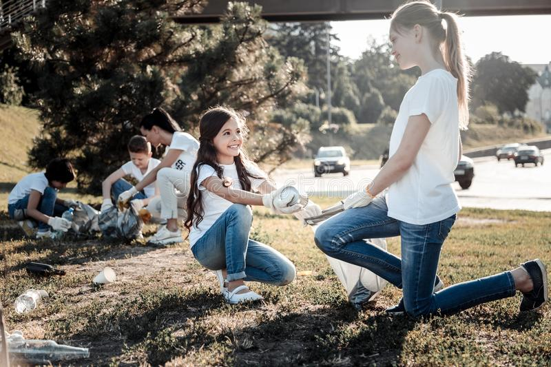 Joyful positive kids volunteering for an eco project. Global problem. Nice joyful positive kids working together and cleaning garbage while volunteering for an stock photo