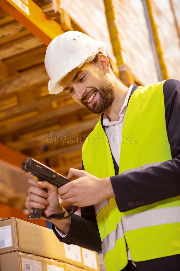 Joyful positive man looking at the scanning device. Professional equipment. Joyful positive man looking at the scanning device while working with goods in the stock images