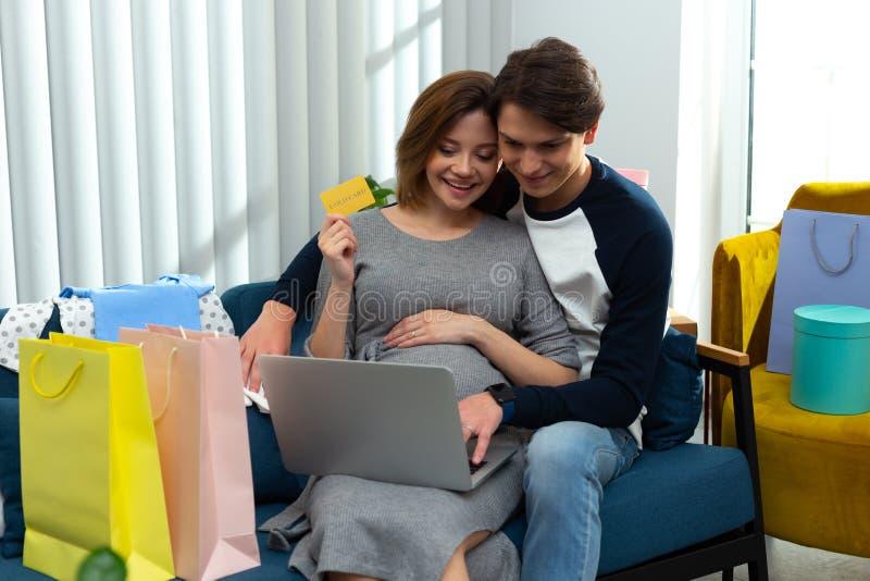 Joyful pregnant woman enjoying shopping online with husband stock images