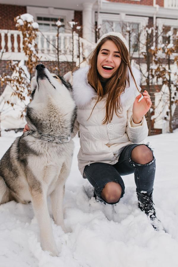 Joyful pretty girl in winter clothes playing with husky dog in snow. Fashionable young woman enjoying cold winter. Weather with domestic pet. Real friendshop royalty free stock photography