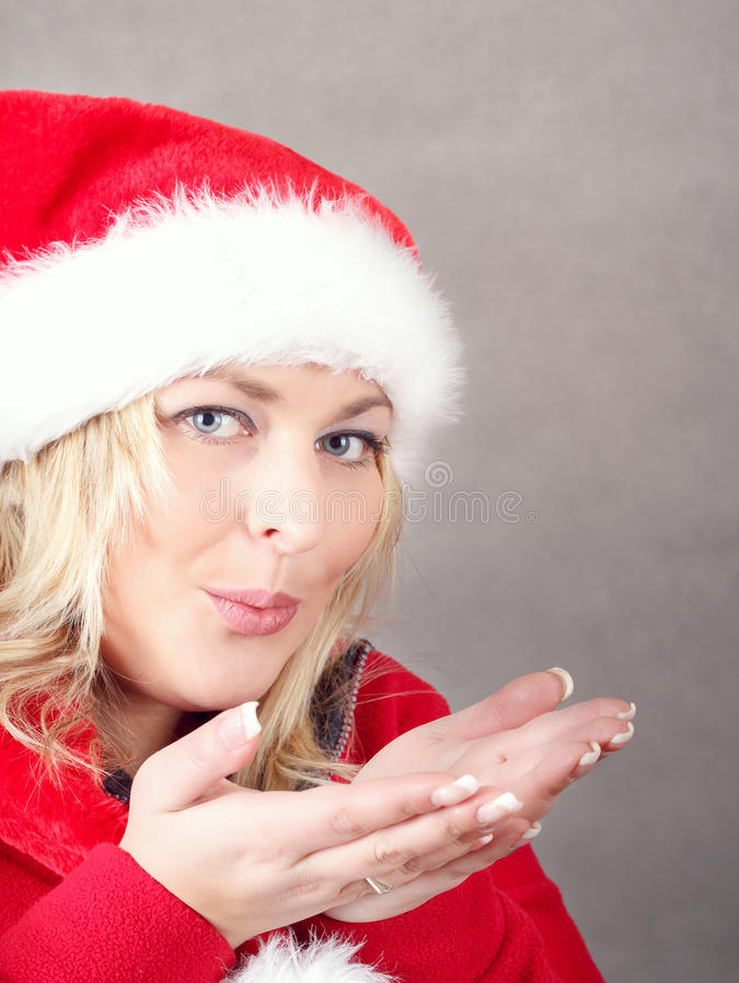 Joyful pretty woman blowing in red santa claus hat