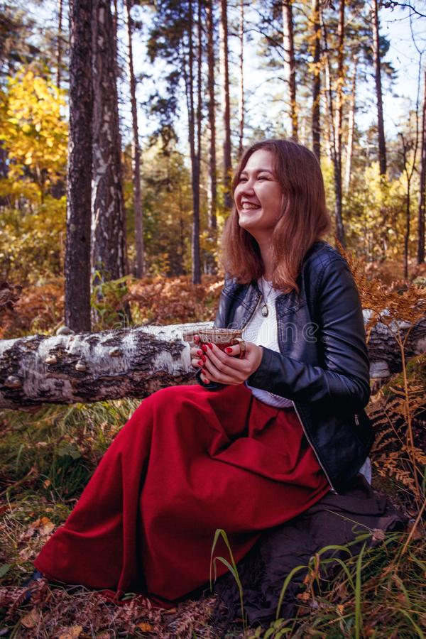 Joyful pretty young happy woman with a cup of tea poses in park. Cheerful girl likes to walk outdoors. Great weekend. Season royalty free stock photography