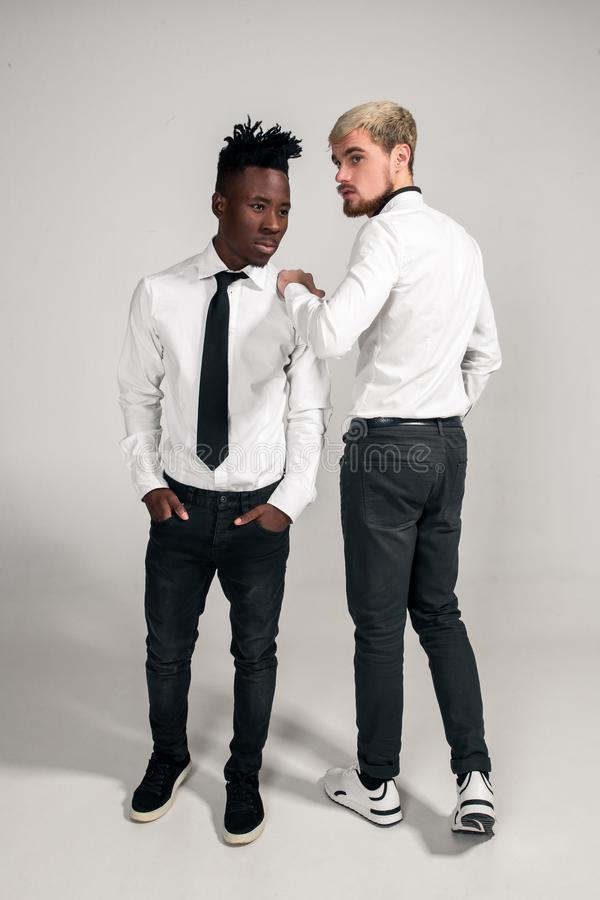 Joyful relaxed african and caucasian boys in white and black office clothes laughing and posing at white studio stock photos