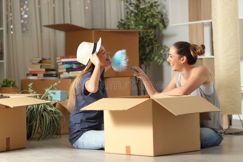 Joyful roommates joking moving home royalty free stock photography