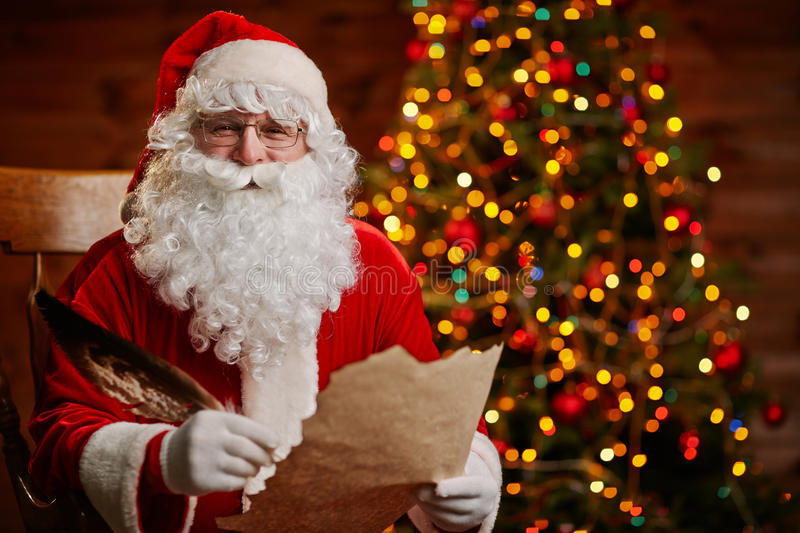 Joyful Santa with letter. Senior man in costume of Santa Claus holding feather and Christmas letter royalty free stock photo