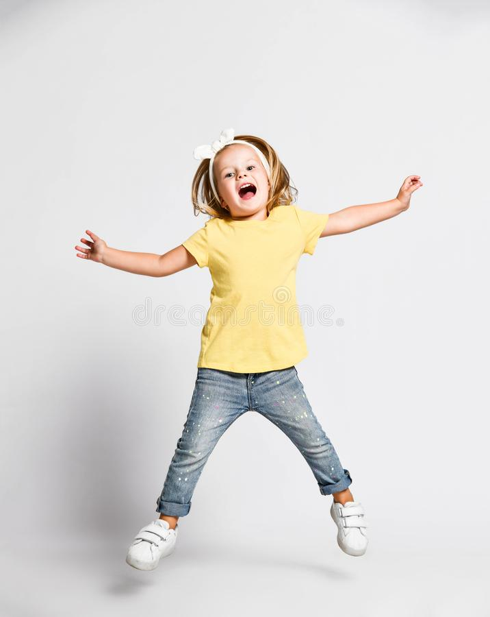 Joyful screaming loud kid baby girl blonde with handband in yellow t-shirt and blue jeans is jumping high, having fun royalty free stock photo