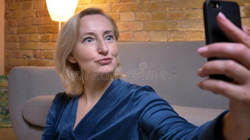 Joyful senior caucasian lady sitting on floor and making funny selfie-photos using smartphone in cozy home atmosphere. royalty free stock images