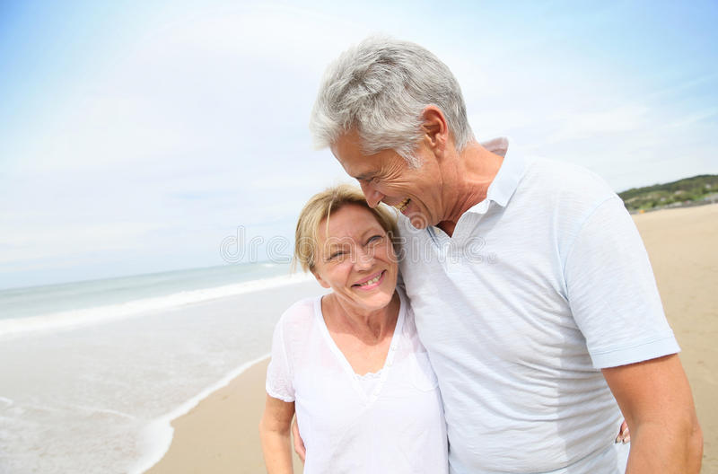 Joyful senior couple enjoying on the beach walking stock photos