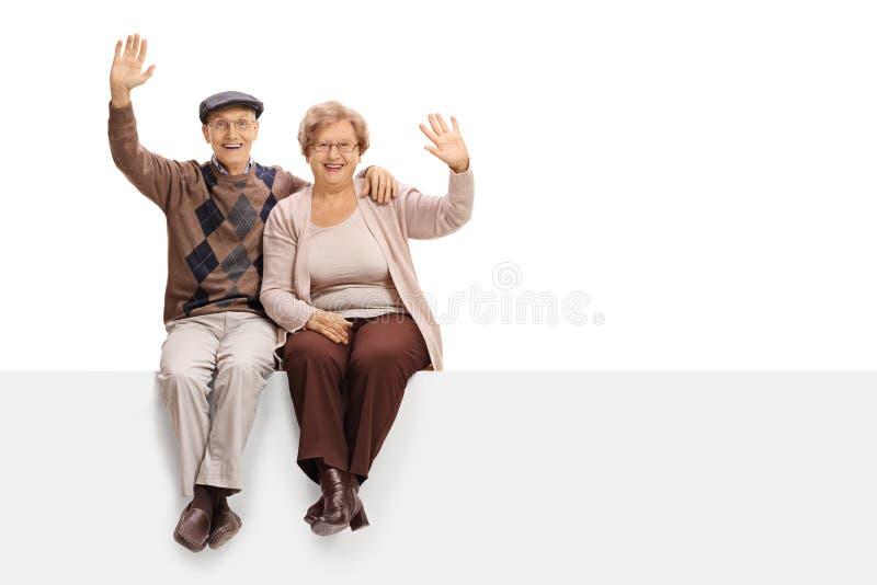 Joyful senior couple sitting on a panel and waving. Isolated on white background stock photo